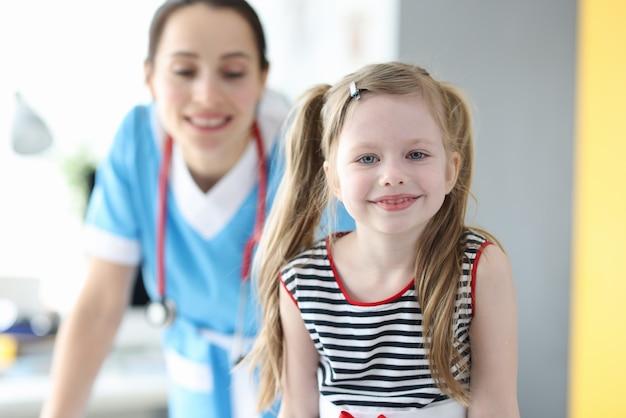 Ritratto di una bambina felice in posa mentre guarda la telecamera dopo una buona consultazione con il pediatra