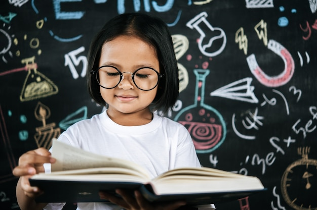 Ritratto felice bambina che legge il libro di testo con la lavagna