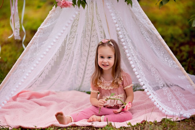 Ritratto di una bambina felice in estate in un parco in un wigwam floreale.