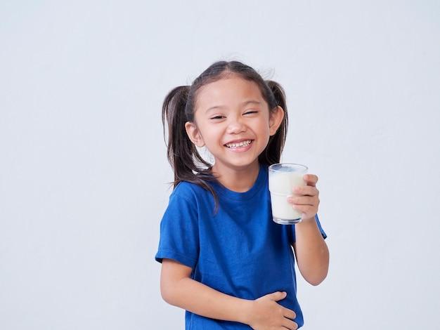 Ritratto di bambina felice con un bicchiere di latte sulla luce