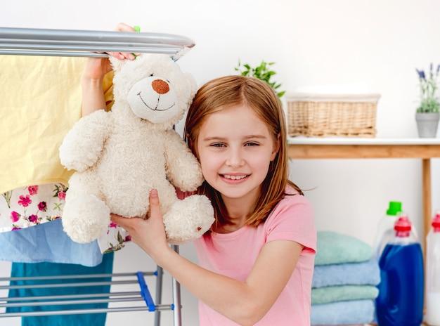 Ritratto di felice bambina con orsacchiotto sull'asciugatrice dopo il lavaggio al chiuso
