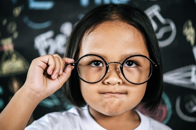 Ritratto di piccolo scolaro felice che indossa gli occhiali