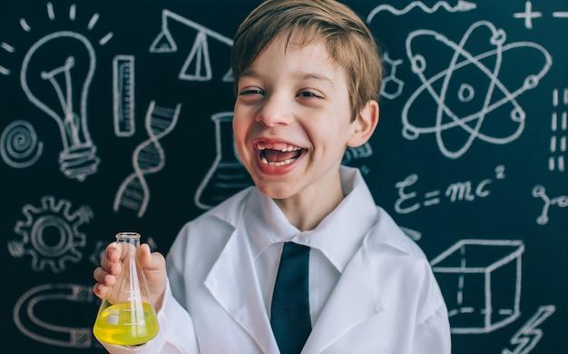 Ritratto di un piccolo scienziato felice che ride mentre tiene in mano una fiaschetta con liquido giallo all'interno