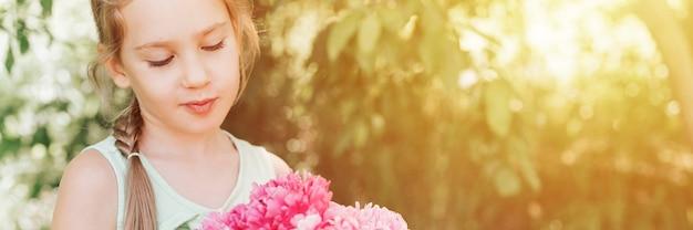 Ritratto di una bambina felice di sette anni, tiene in mano e ama vedere un bouquet