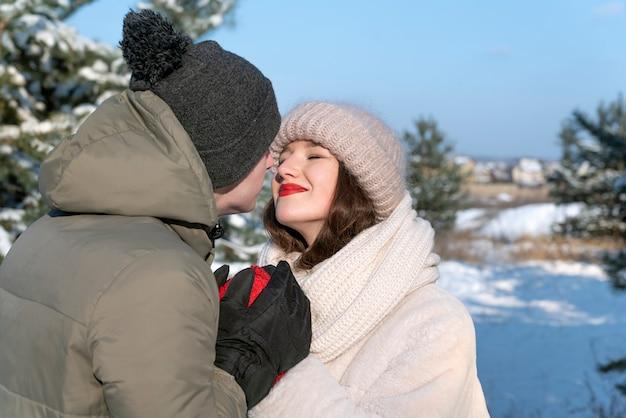 Ritratto di felice coppia di innamorati nella foresta invernale. tenerezza e amore.