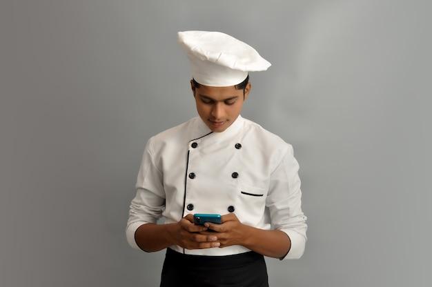 Ritratto di un felice chef maschio vestito in uniforme che tiene in mano un cellulare e invia sms o chat