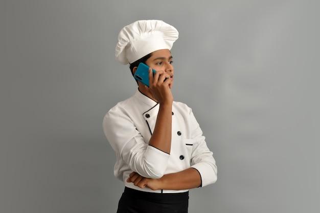 Ritratto di uno chef maschio felice vestito in uniforme che parla al telefono