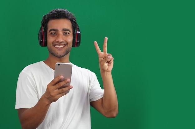 Ritratto di un uomo felice che celebra il successo del suo risultato dando segno di vittoria