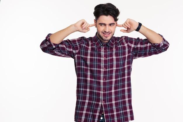 Ritratto di un uomo felice che si copre le orecchie con le dita isolate su un muro bianco