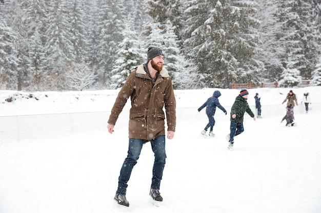 Ritratto di un uomo felice che pattina sul ghiaccio all'aperto