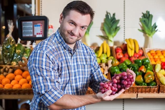 Ritratto di uomo felice in camicia che mostra un grappolo d'uva nel supermercato. scatole con frutta e verdura