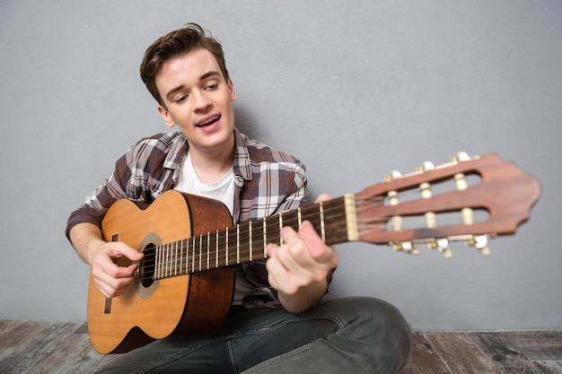 Ritratto di un uomo felice seduto sul pavimento e che suona la chitarra su un muro grigio