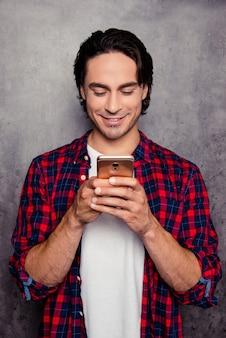Ritratto di uomo felice teping messaggio sullo smartphone su uno spazio grigio