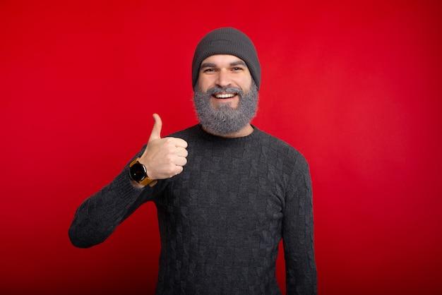 Ritratto dell'uomo felice con la barba bianca che mostra i pollici in su sopra spazio rosso