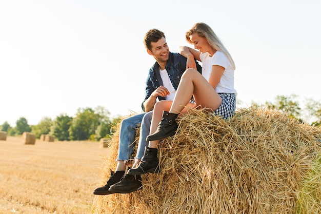 Ritratto di uomo felice e donna seduta sul grande pagliaio in campo d'oro, durante la giornata di sole