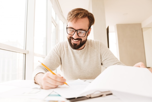 Ritratto di un uomo felice che lavora con i documenti