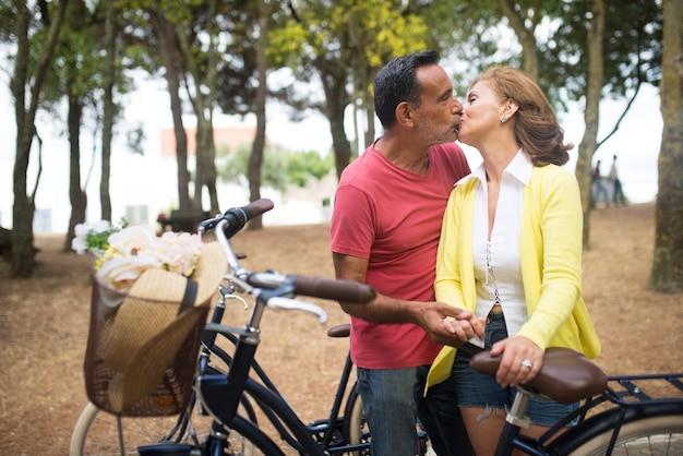 Ritratto di amanti maturi felici che si baciano nel parco