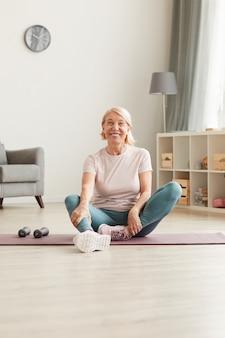 Ritratto di donna matura felice che si siede sul pavimento e che riposa dopo l'allenamento sportivo a casa lei sorride