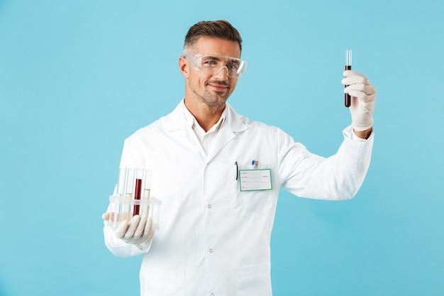 Ritratto di felice medico con gli occhiali che tengono le provette con sangue, in piedi isolato sopra la parete blu