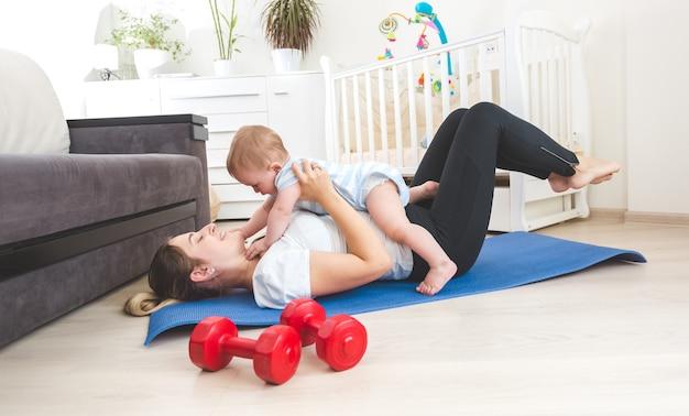 Ritratto di madre felice che fa esercizio a casa e si diverte con il suo bambino