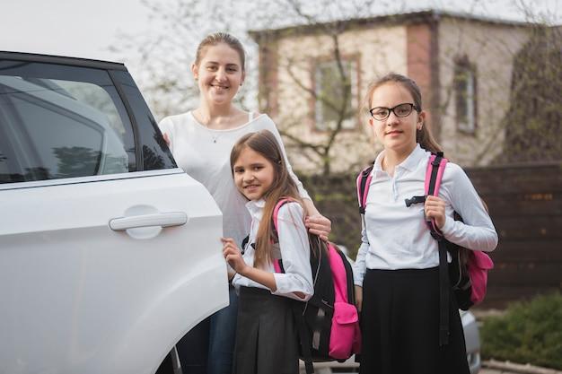 Ritratto di madre felice e due ragazze con zaini in posa in macchina