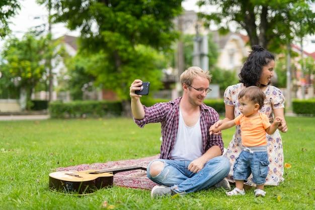 Ritratto di felice famiglia multietnica con un bambino che lega insieme all'aperto