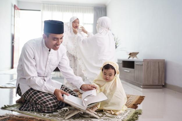 Ritratto di felice famiglia musulmana con bambini che leggono il corano e pregano insieme a casa