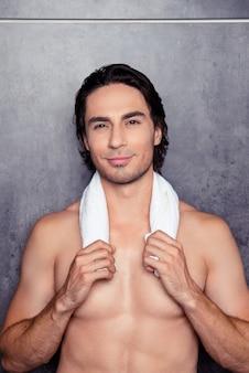 Ritratto di uomo atletico nudo felice con un asciugamano bianco