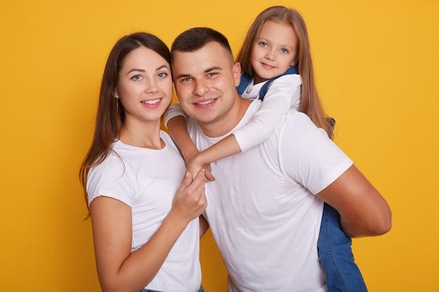 Ritratto di genitori felici, papà porta le loro belle figlie sulla schiena.
