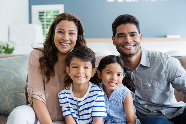 Ritratto dei genitori e dei bambini felici che si siedono sul sofà in salone