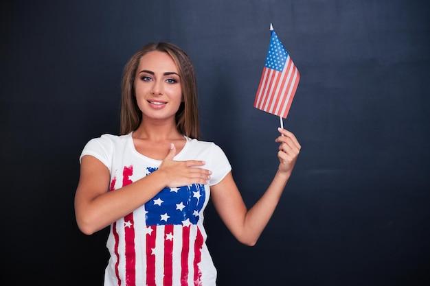 Ritratto di una ragazza patriottica felice che tiene la bandiera degli stati uniti su uno spazio grigio