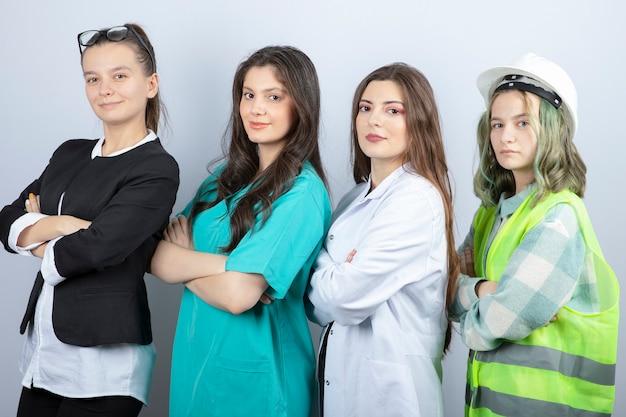 Ritratto di persone felici di diverse professioni in piedi con le braccia incrociate su sfondo bianco. foto di alta qualità