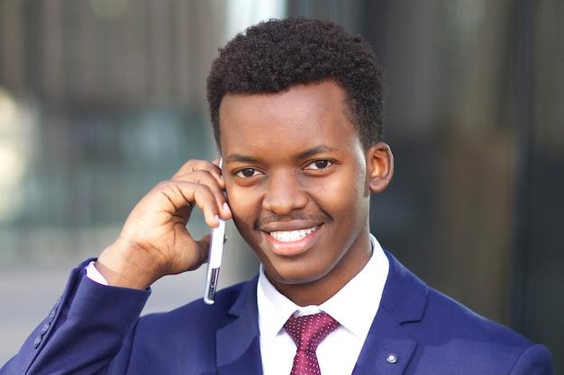 Ritratto dell'uomo d'affari afroamericano africano nero positivo felice che comunica sul telefono mobile delle cellule in vestito convenzionale