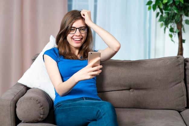 Il ritratto della bella donna di successo giovane della ragazza emozionante positiva felice in vetri sta sorridendo
