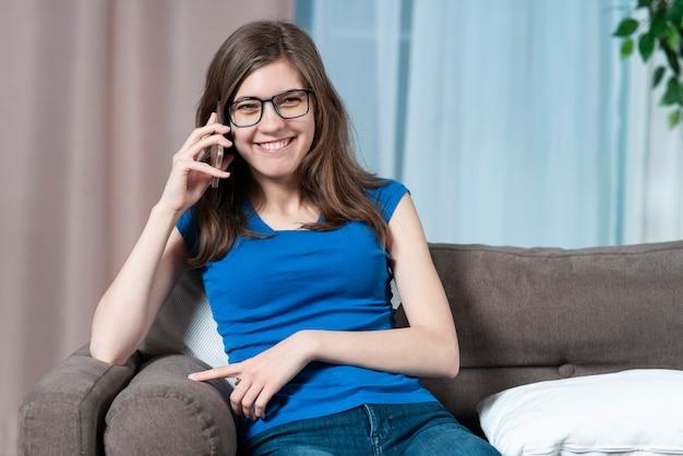 Il ritratto della giovane bella donna graziosa gioiosa della ragazza positiva felice sta parlando sul suo cellulare