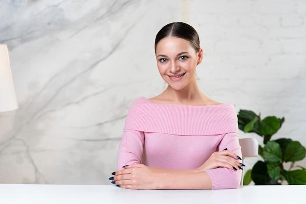 Ritratto di felice ragazza positiva giovane bella donna seduta sul tavolo a casa e sorridente con lei