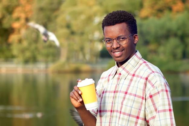 Ritratto di felice positivo giovane afroamericano nero uomo afro in camicia sorridente in estate o