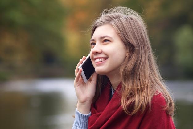Ritratto di felice giovane donna positiva in chat, parlando sul suo cellulare smart phone, avendo una buona