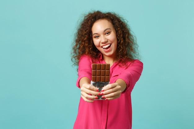 Il ritratto della ragazza abbastanza africana felice in vestiti casuali tiene in mano la barretta di cioccolato isolata sul fondo della parete turchese blu in studio. persone sincere emozioni, concetto di stile di vita. mock up copia spazio.