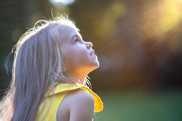 Ritratto della ragazza felice del bambino grazioso che sorride all'aperto godendo calda giornata estiva di sole.
