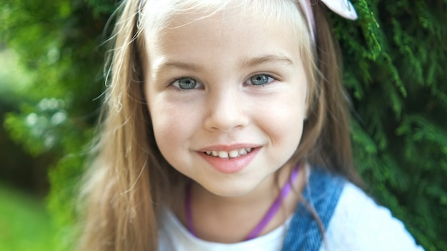Ritratto di ragazza felice bambino grazioso in piedi nel parco estivo guardando a porte chiuse.