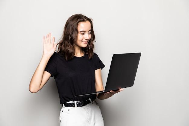 Ritratto di una ragazza graziosa felice che tiene il computer portatile e che fluttua mentre ha conversazione video isolata sopra il muro grigio