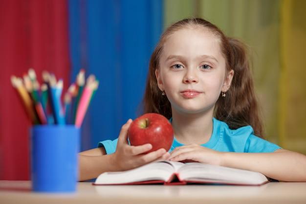 Ritratto della ragazza graziosa felice che tiene una mela rossa nell'aula