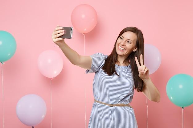 Ritratto di donna graziosa felice in abito blu che fa selfie sul telefono cellulare che mostra il segno di vittoria su sfondo rosa con mongolfiere colorate. festa di compleanno, concetto di emozioni sincere della gente.
