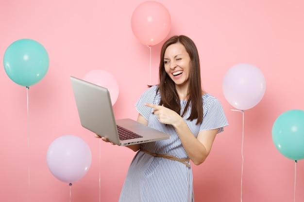 Ritratto di donna graziosa felice in abito blu tenere utilizzando il computer pc portatile che punta il dito indice lampeggiante su sfondo rosa con mongolfiere colorate. festa di compleanno persone emozioni sincere.
