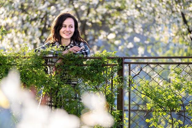 Ritratto di donna abbastanza giovane felice all'aperto il giorno pieno di sole di primavera.