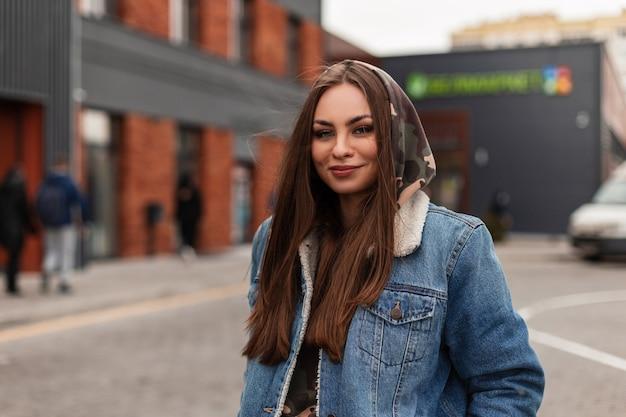 Ritratto felice piuttosto giovane donna con capelli castani nel cappuccio in giacca di jeans blu alla moda all'aperto in città. la ragazza europea alla moda si diverte a camminare per strada. sguardo quotidiano. collezione primaverile.
