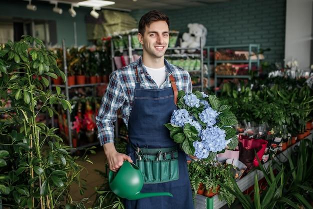 Ritratto di giardiniere professionista felice che tiene vaso di fiori e annaffiatoio