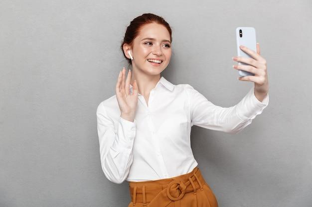 Ritratto di felice imprenditrice rossa 20s indossando auricolari tenendo e guardando lo smartphone in ufficio isolato su gray