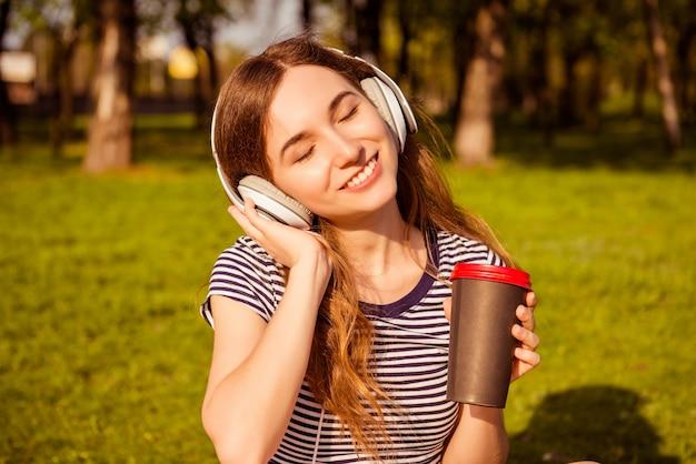 Ritratto di donna felice rilassata ascoltando musica in cuffia e bere caffè